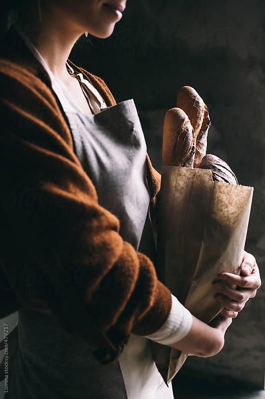 Bakery Employee Holding Bread by Lumina for Stocksy United