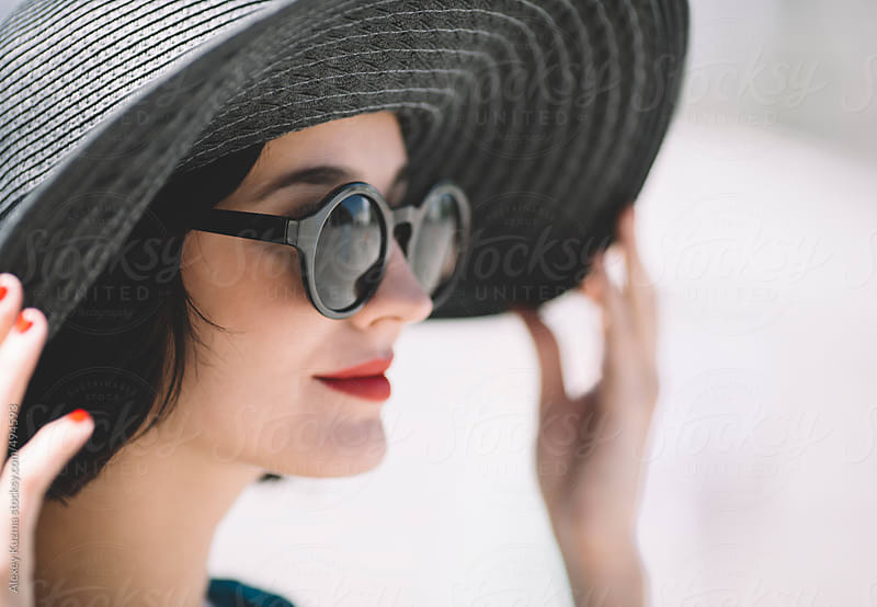 closeup of young woman with black hat and retro sunglasses by Alexey Kuzma for Stocksy United