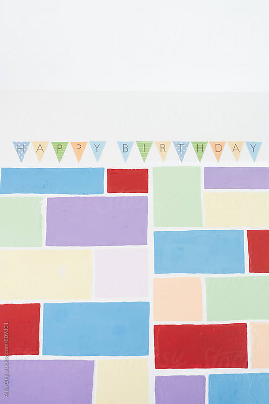 Happy birthday bunting on colourful wall by Alita Ong for Stocksy United