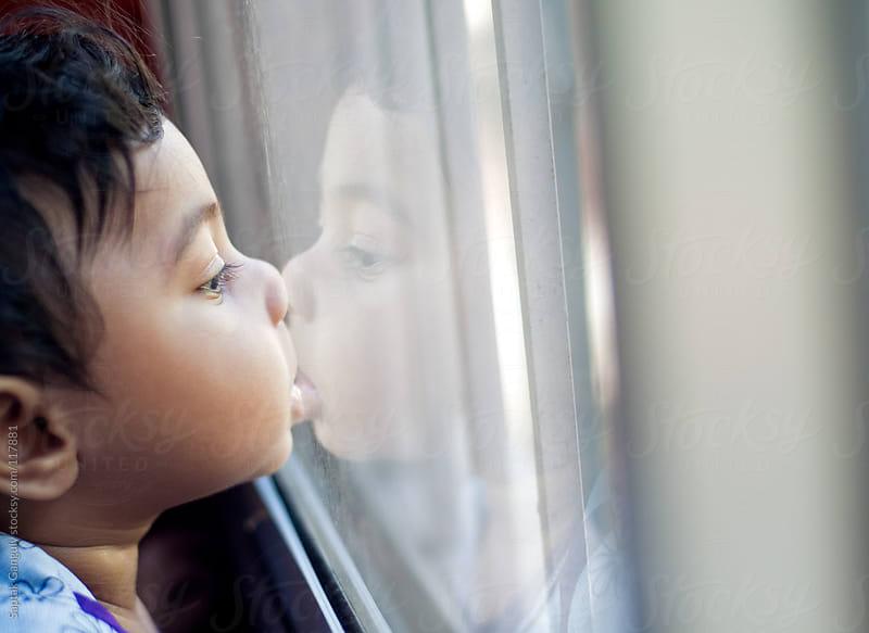 Cute baby girl looking through glass window by Saptak Ganguly for Stocksy United