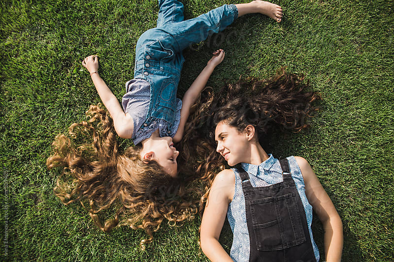 Mother and daughter laying on the green grass looking at each other  by Irina Efremova for Stocksy United