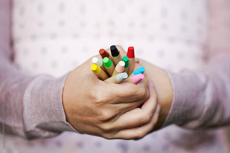 Woman's hands holding plenty of colourful wax crayons  by Laura Stolfi for Stocksy United