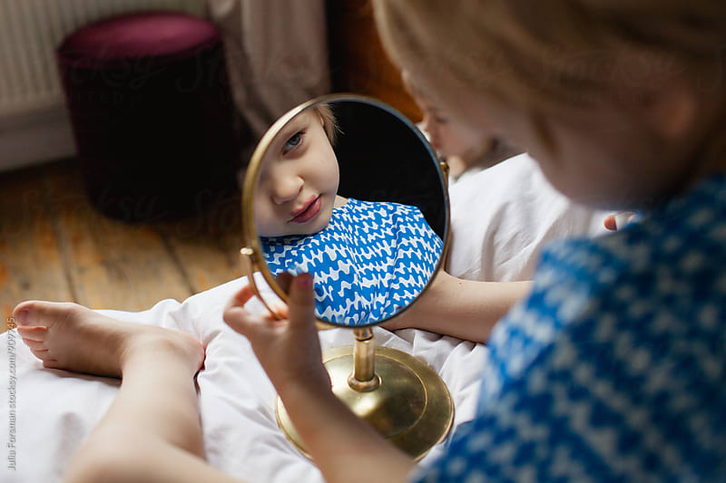Young girl checks the lipstick she has put on in a round mirror. by Julia Forsman for Stocksy United