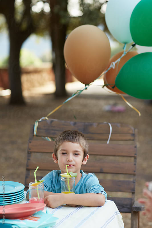 Child sitting on a big  seat with balloons for a party by Miquel Llonch for Stocksy United