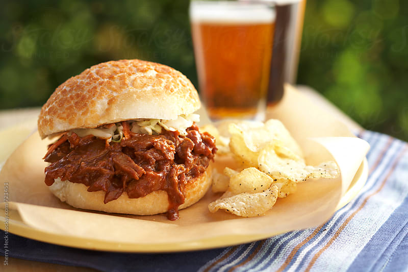 BBQ pulled pork on bun with potato chips and beers by Sherry Heck for Stocksy United