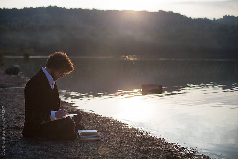 Young man, sitting cross-legs on a beach by a lake, writing. by Luca Di Lotti for Stocksy United