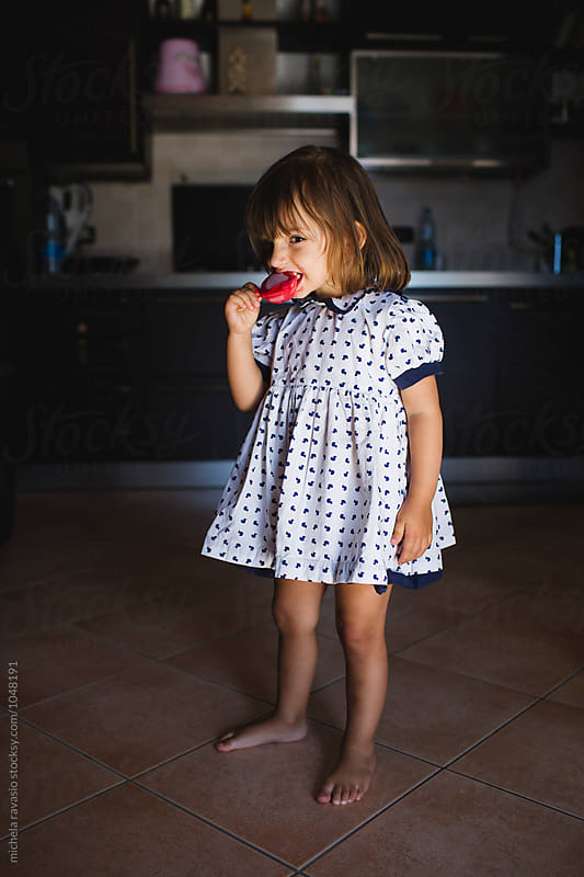 Standing child bites a strawberry ice cream by michela ravasio for Stocksy United