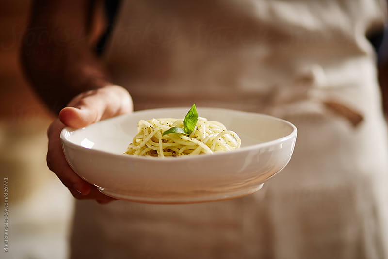 Chef holding rice spaghetti with pesto sauce by Martí Sans for Stocksy United