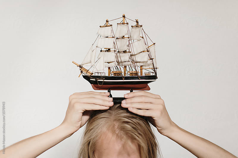 man holding model ship on his head with both hands by Nicole Mason for Stocksy United