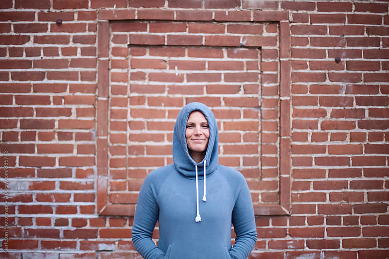 Woman in hooded sweatshirt in front of brick wall by Carleton Photography for Stocksy United