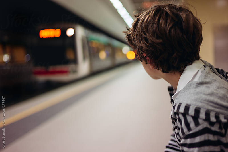Boy watching a train arrive in a train station at night by Angela Lumsden for Stocksy United