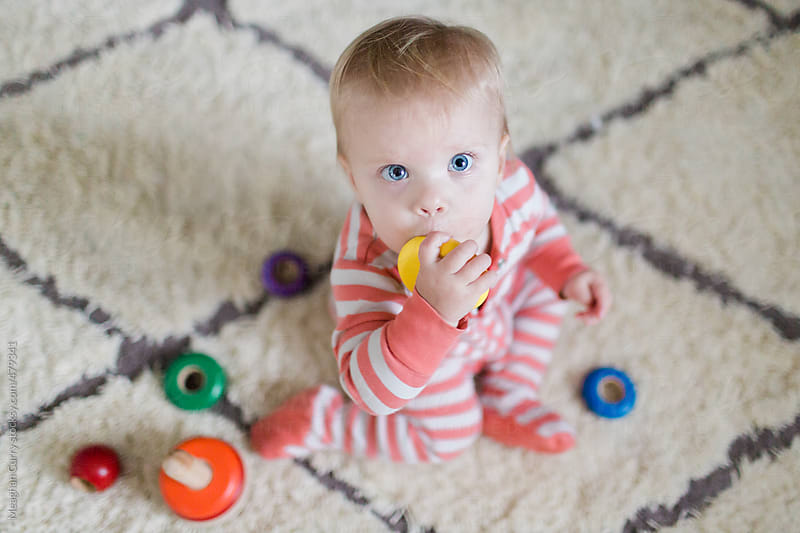 aerial view of baby playing with a wooden toy in a living room by Meaghan Curry for Stocksy United
