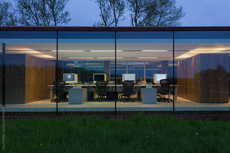 Glass facade to an office at twilight. Looking inward by Paul Phillips for Stocksy United