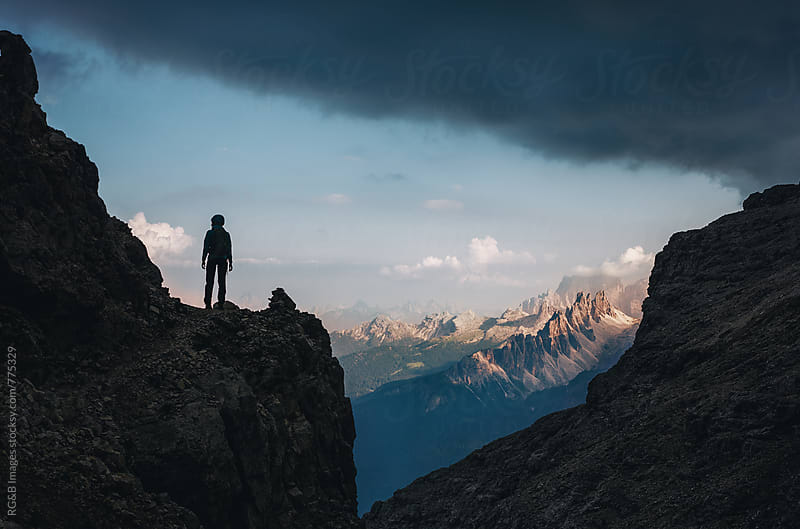 Mountaineer silhouette walking on a high mountain trail by RG&B Images for Stocksy United
