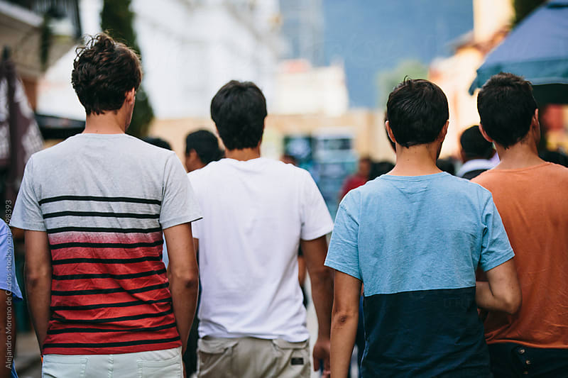 Back view of four young men in t-shirts walking down a busy street by Alejandro Moreno de Carlos for Stocksy United