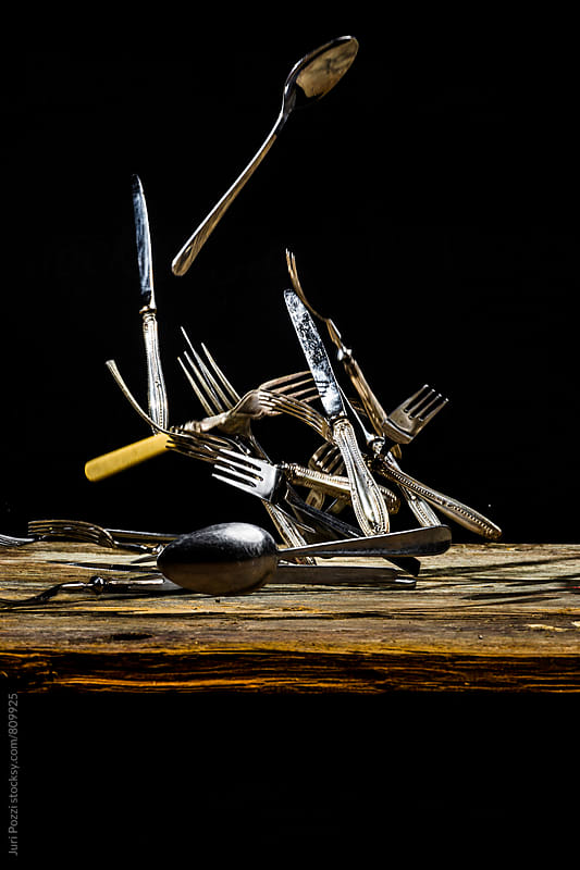 Cutlery falling on a wooden table by Juri Pozzi for Stocksy United