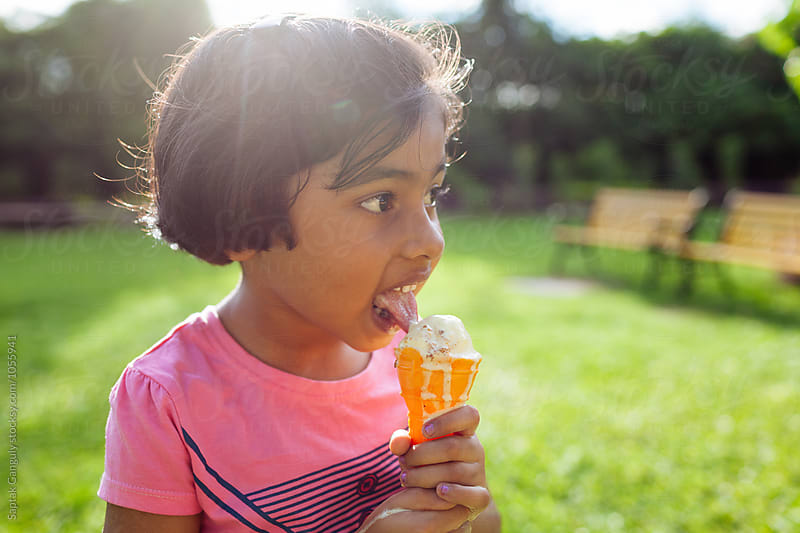 Little girl enjoying an ice cream outdoors by Saptak Ganguly for Stocksy United