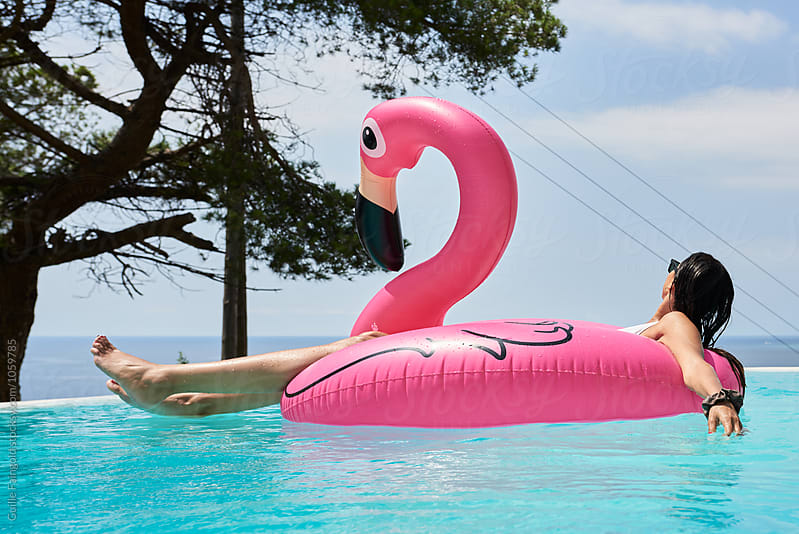 Brunette on flamingo air mattress at pool by Guille Faingold for Stocksy United