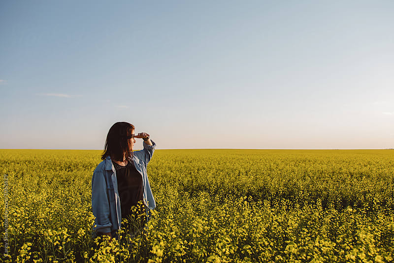 Female farmer looking out to field of canola by Carey Shaw for Stocksy United