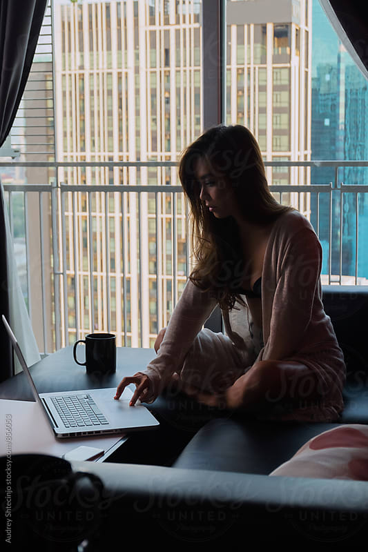 Asian woman in relaxed home atmosphere using her laptop with city in background. by Marko Milanovic for Stocksy United