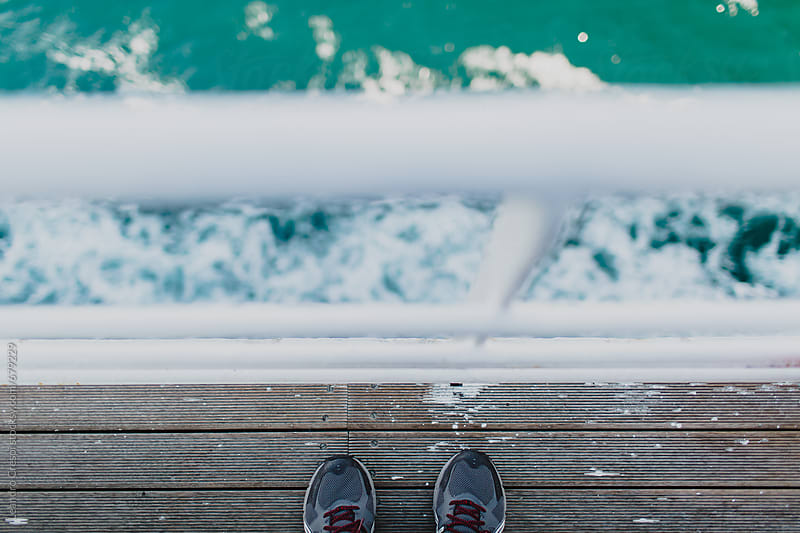 Shoes seen from above, at the edge of a boat deck by Leandro Crespi for Stocksy United
