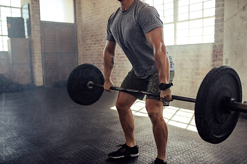 Muscular young man lifting barbell at gym by Jacob Ammentorp Lund for Stocksy United