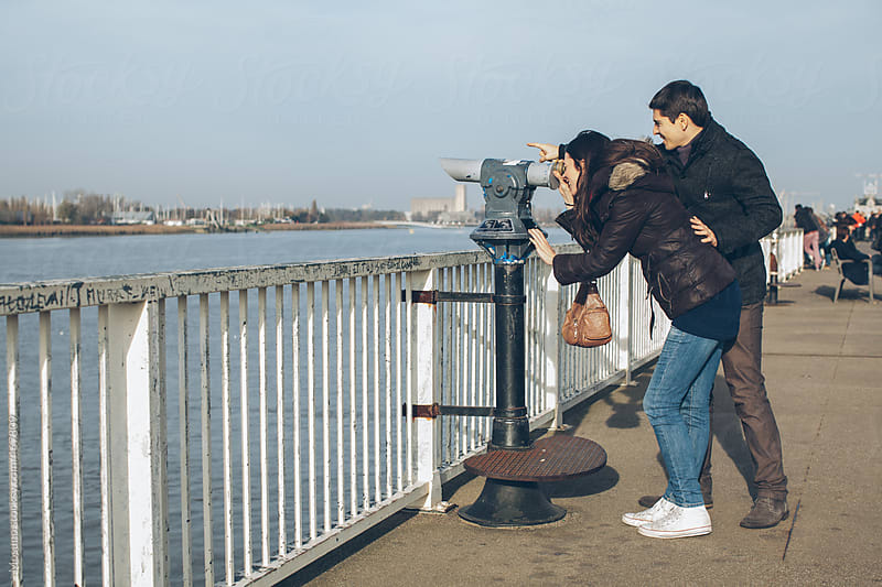Tourist Couple Looking Through Spyglass  by Mosuno for Stocksy United