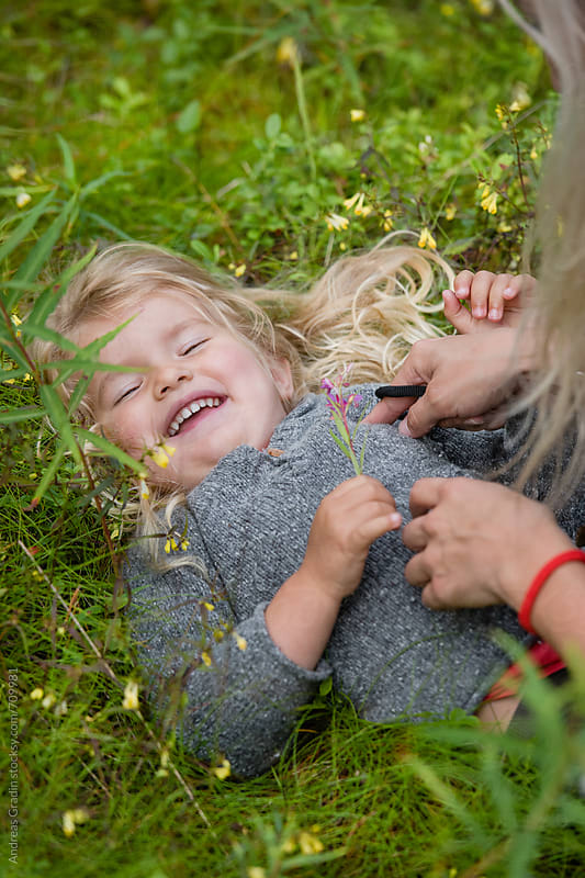 playing in the grass by Andreas Gradin for Stocksy United