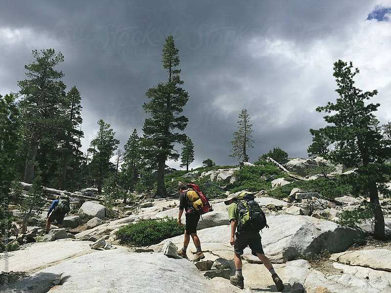 Three backpackers hiking in the Desolation Wilderness by Paul Edmondson for Stocksy United