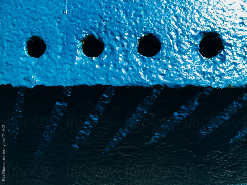 Detail of painted blue metal machinery, holes casting shadows by Paul Edmondson for Stocksy United