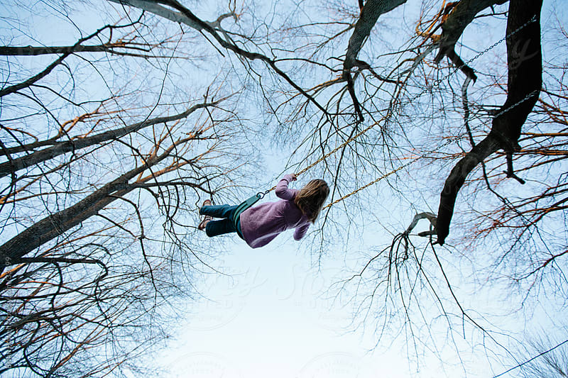 a little girl swinging under big trees by Brian Powell for Stocksy United