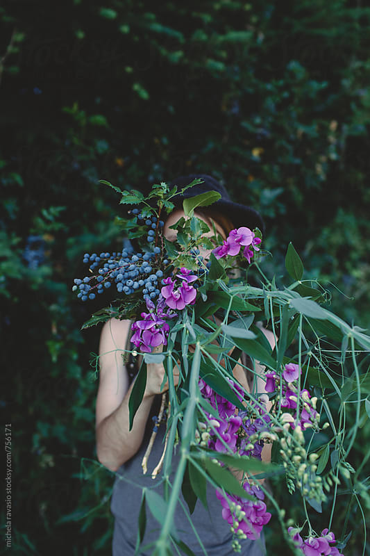 Young woman hidden by plants and wild flowers picked in the forest by michela ravasio for Stocksy United