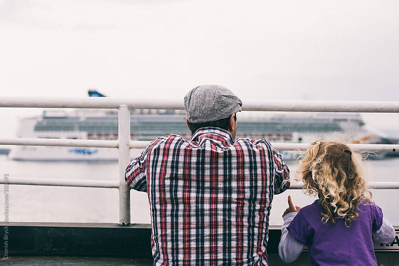 Father and daughter watch a ferry boat. by Cherish Bryck for Stocksy United