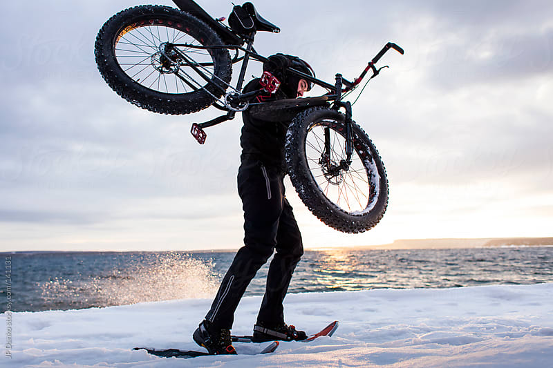 Extreme Winter Sport Man With Snowshoes Carrying Fat Bike in Snow by JP Danko for Stocksy United