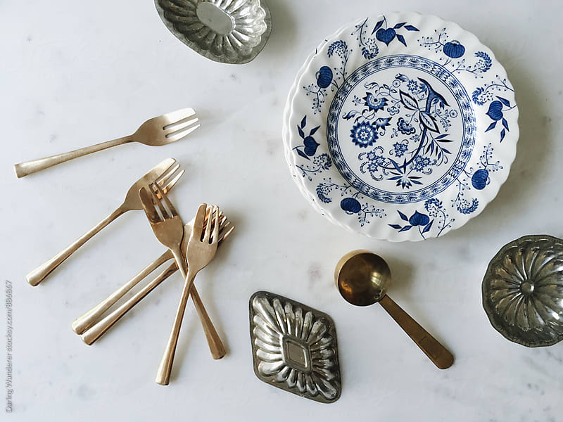 Collection of vintage forks, plates and bakeware on marble table by Daring Wanderer for Stocksy United