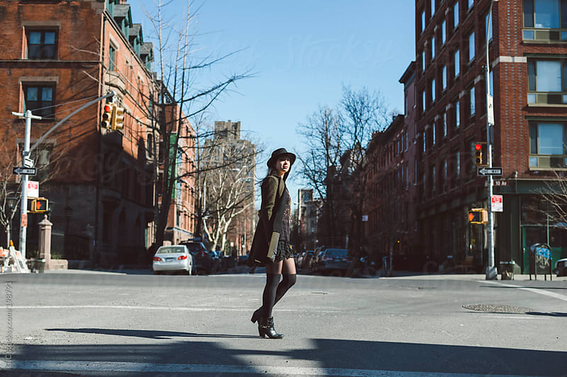 Young woman walking in the streets of New York City by GIC for Stocksy United