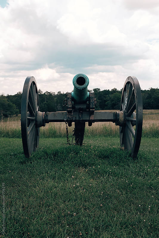An old antique historic Civil War cannon in a field of green grass and blue skies overhead by Greg Schmigel for Stocksy United