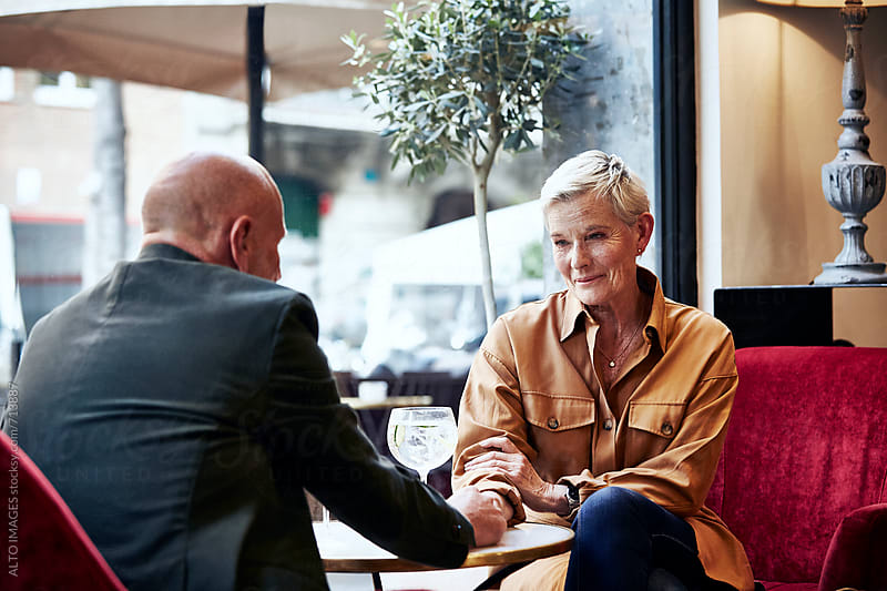 Senior Woman Holding Man's Hand In Restaurant by ALTO IMAGES for Stocksy United