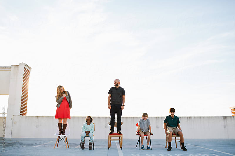 Family Standing in Chair by Erin Drago for Stocksy United