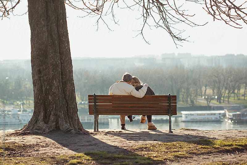 Senior couple sitting at the park by Jelena Jojic Tomic for Stocksy United