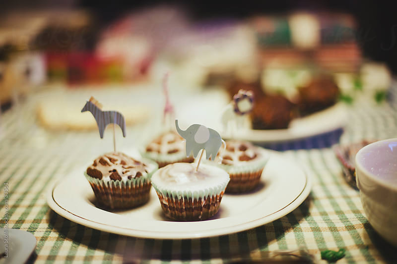 Home made cupcakes with animal shaped toppers on party table by Laura Stolfi for Stocksy United