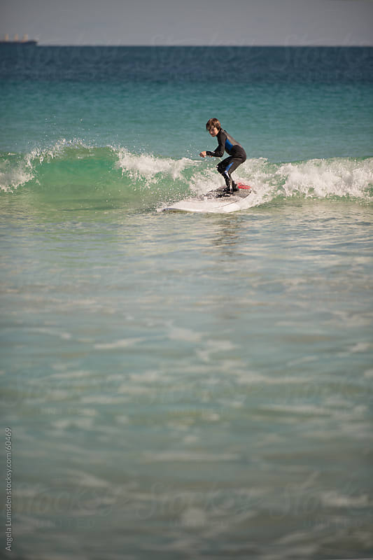 Small boy catches a wave on a stand up paddle board by Angela Lumsden for Stocksy United