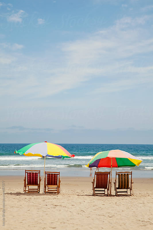 Two colourful parasols with chairs  on a empty beach with the sea on the background by Ivo de Bruijn for Stocksy United