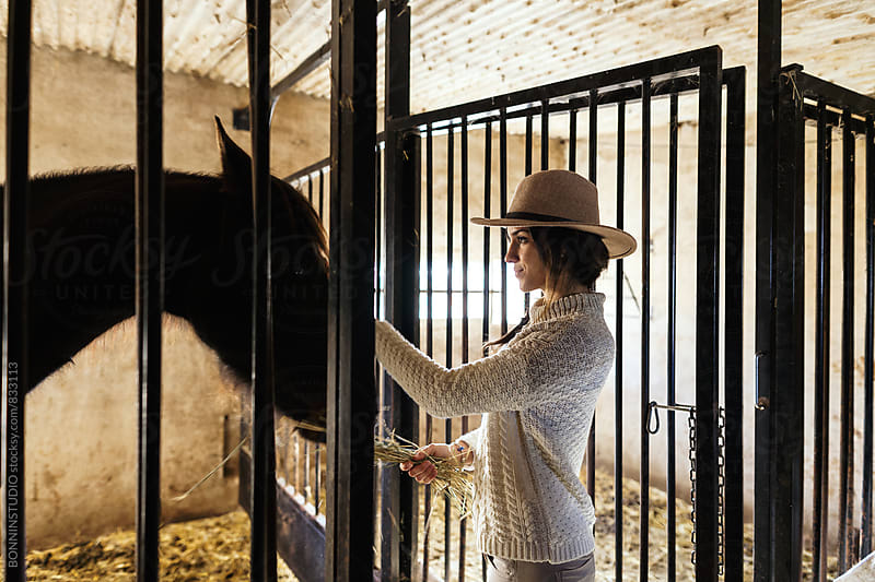 Woman farmer feeding her horse in stable. by BONNINSTUDIO for Stocksy United