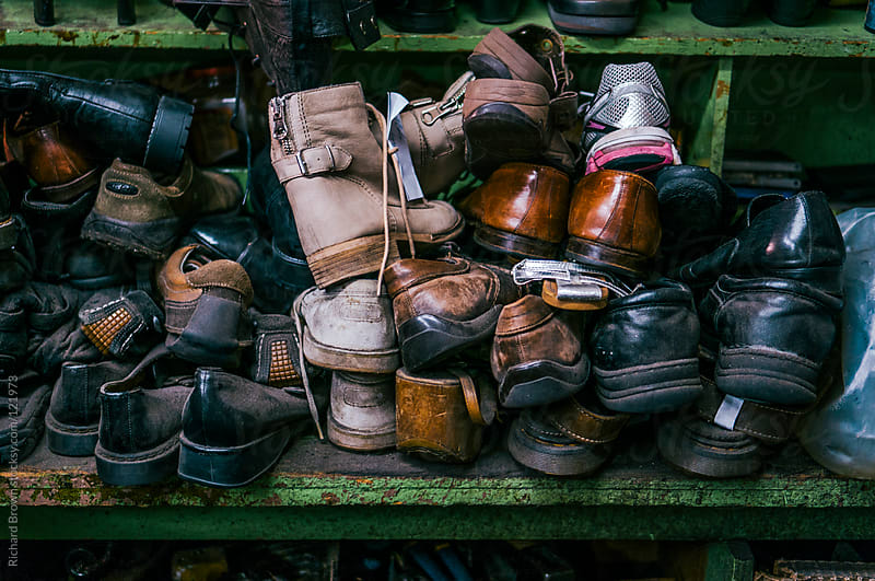 A bunch of old shoes sitting on a shelf by Richard Brown for Stocksy United