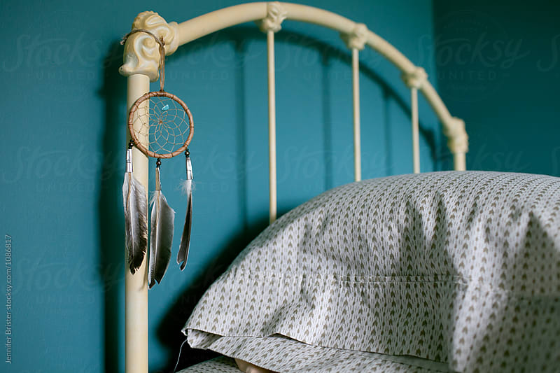 Dreamcatcher hangs on bed frame by Jennifer Brister for Stocksy United
