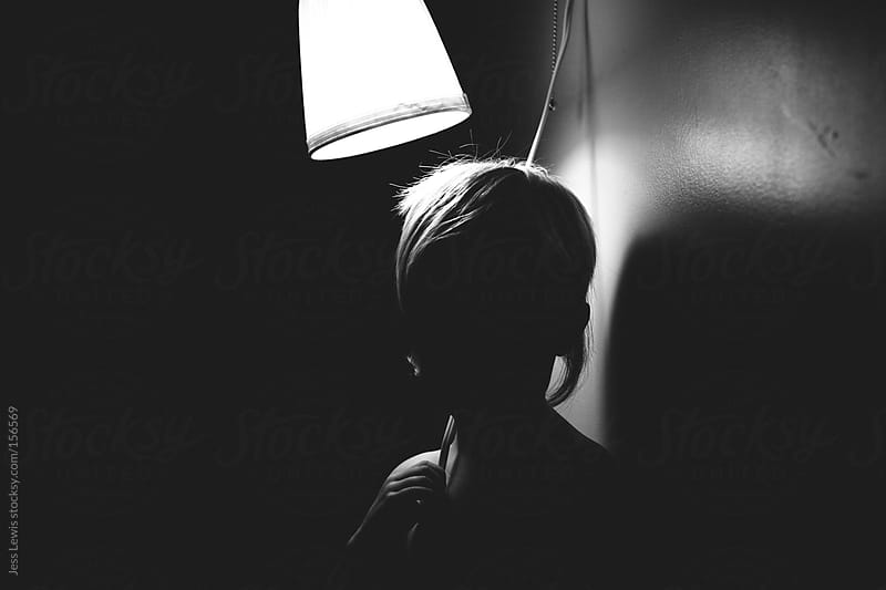 silhouette of child standing under a lamp by Jess Lewis for Stocksy United