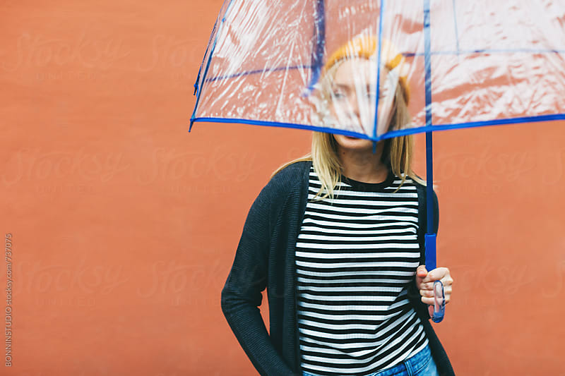 Woman covering her face with an umbrella in front of an orange wall. by BONNINSTUDIO for Stocksy United