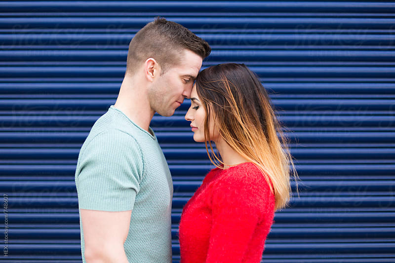 Young Couple Standing Close Against a Blue Shutter by HEX . for Stocksy United