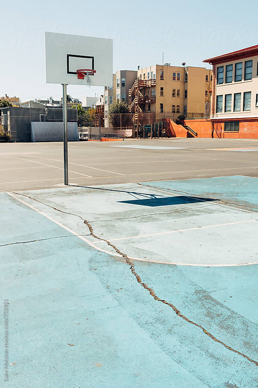 Solitary Basketball Hoop On Light Blue Asphalt Court In School Playground by Luke Mattson for Stocksy United